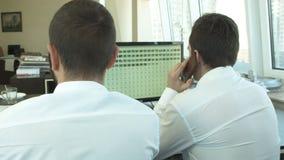 2 бизнесмена обсуждают с работой клиента телефоном акции видеоматериалы