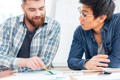 2 бизнесмена обсуждая бизнес-план в офисе Стоковая Фотография