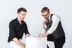2 бизнесмена обсуждая задачи сидя и смотря дело Стоковое Изображение RF