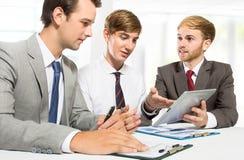 3 бизнесмена обсуждая новый план на офисе Стоковые Изображения RF