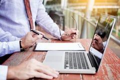 2 бизнесмена обсуждая строгающ задачи с портативным компьютером si Стоковое Фото