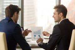 2 бизнесмена обсуждая финансовый отчет с диаграммами диаграмм, Стоковое фото RF