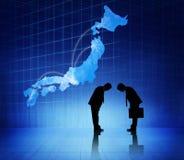 2 бизнесмена обхватывая головы друг к другу и Японию Cartograp Стоковое фото RF