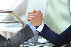 2 бизнесмена отжимают один другого рук на передней предпосылке Стоковые Изображения RF