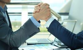 2 бизнесмена отжимают один другого рук на передней предпосылке Стоковое Изображение