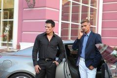 2 бизнесмена приближают к роскошному автомобилю, сотовому телефону Стоковые Фотографии RF
