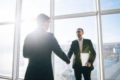 2 бизнесмена приветствуя в солнечной комнате офиса Стоковые Изображения