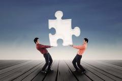 2 бизнесмена приносят головоломку напольную Стоковые Изображения