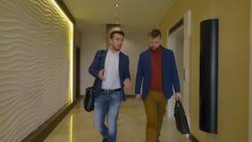 2 бизнесмена приходя вне лифт и идя на длинную залу в гостинице дела акции видеоматериалы