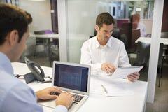 2 бизнесмена работая в офисе с ПК компьтер-книжки и таблетки Стоковые Изображения RF