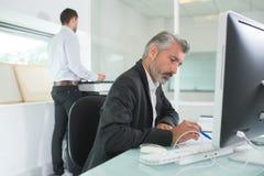 2 бизнесмена работая в офисе Стоковые Изображения