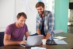 2 бизнесмена работая на компьтер-книжке в офисе совместно Стоковое Изображение RF