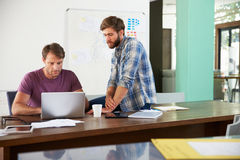 2 бизнесмена работая на компьтер-книжке в офисе совместно Стоковое Изображение