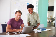 2 бизнесмена работая на компьтер-книжке в офисе совместно Стоковое фото RF
