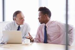 2 бизнесмена работая на компьтер-книжке на таблице зала заседаний правления Стоковое Фото