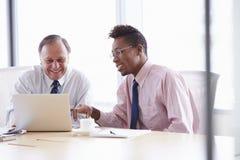 2 бизнесмена работая на компьтер-книжке на таблице зала заседаний правления Стоковые Фотографии RF
