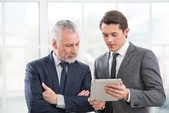 2 бизнесмена работая на планшете Стоковые Изображения RF