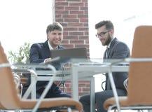 2 бизнесмена работая совместно используя компьтер-книжку на деловой встрече в офисе Стоковое Изображение RF