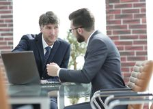 2 бизнесмена работая совместно используя компьтер-книжку на деловой встрече в офисе Стоковые Фотографии RF