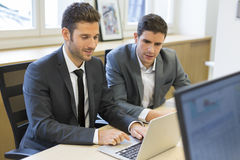 2 бизнесмена работая совместно на проекте в офисе Стоковое фото RF