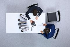 2 бизнесмена сидя на таблице, осматривают сверху Bookkeeper или финансовый контролер делая отчет, высчитывая o Стоковое Изображение RF