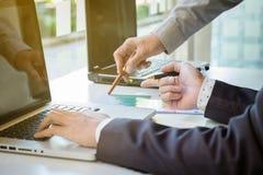 2 бизнесмена смотря отчет и имея обсуждение внутри  Стоковое Изображение