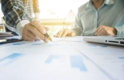 2 бизнесмена смотря отчет и имея обсуждение внутри  Стоковая Фотография RF