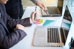 2 бизнесмена смотря отчет и имея обсуждение внутри  Стоковая Фотография
