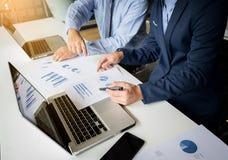 2 бизнесмена смотря отчет и имея обсуждение внутри  Стоковое фото RF