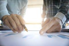 2 бизнесмена смотря отчет и имея обсуждение внутри  Стоковые Изображения RF