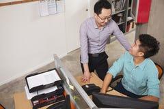 2 бизнесмена смотря один другого и усмехаться, работая в офисе Стоковое Изображение RF