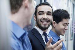 3 бизнесмена стоя в ряд и говоря на метро Стоковая Фотография