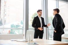 2 бизнесмена стоя и говоря в офисе Стоковое Фото