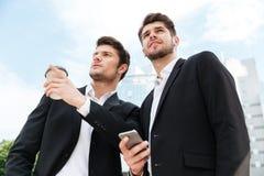 2 бизнесмена с взятия кофе и сотовым телефоном прочь outdoors Стоковое Фото