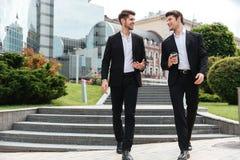 2 бизнесмена с взятия кофе прочь идя и говоря outdoors Стоковые Изображения