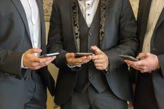 3 бизнесмена с мобильными телефонами Люди с современными мобильными телефонами Стоковое Изображение RF