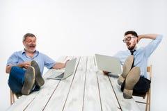 2 бизнесмена с ногами над таблицей работая на компьтер-книжках Стоковая Фотография RF