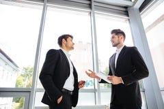 2 бизнесмена с таблеткой и мобильным телефоном говоря в офисе Стоковые Фото