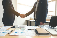 2 бизнесмена тряся руки во время встречи для подписания согласования и для того чтобы стать деловым партнером, предприятиями, ком Стоковые Изображения RF