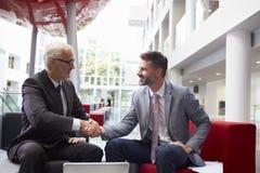 2 бизнесмена тряся руки в лобби современного офиса Стоковая Фотография