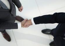 2 бизнесмена тряся руки в офисе Стоковые Изображения