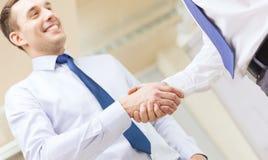 2 бизнесмена тряся руки в офисе Стоковые Фотографии RF