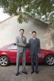 2 бизнесмена тряся руки перед красным автомобилем Стоковые Фото