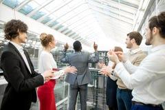 2 бизнесмена тряся руки пока их коллеги аплодируя и усмехаясь Стоковое Фото