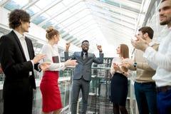 2 бизнесмена тряся руки пока их коллеги аплодируя и усмехаясь Стоковая Фотография