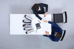 2 бизнесмена тряся руки пока сидящ на таблице, осматривают сверху Bookkeeper или финансовое makin контролера Стоковая Фотография RF
