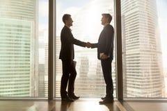 2 бизнесмена тряся руки стоя около большого окна, городского ci Стоковая Фотография RF