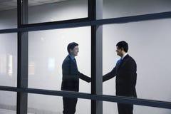 2 бизнесмена тряся руки, увиденную до конца стеклянную стену Стоковые Изображения