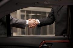 2 бизнесмена тряся руку через окно автомобиля Стоковое Изображение