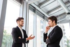 2 бизнесмена усмехаясь и говоря в офисе Стоковая Фотография